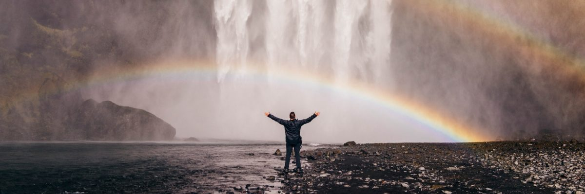 man standing in front of rainbows created by waterfalls