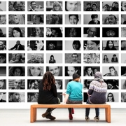 black and white photos of different faces covering a large wall, with three women on a bench looking at them