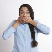 woman covering mouth with wide, excited eyes