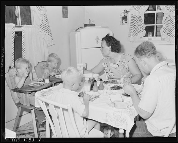 599px-James_Jasper,_motor_brakeman,_and_his_family_eat_dinner_in_their_kitchen_in_home_in_company_housing_project._Koppers..._-_NARA_-_540913