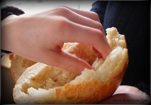 child's hand taking communion bread