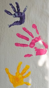 handprints in paint on a white wall