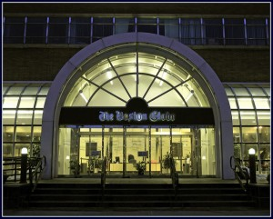 the front doors of the Boston Globe building, lit up at night