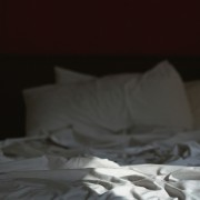 rumpled, unmade bed in shadow