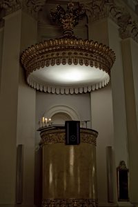 tall pulpit with lighted, round sound board above it