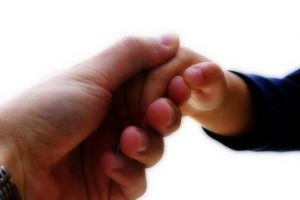 Adult hand holding a child's hand