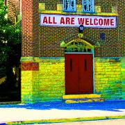 'All Are Welcome' sign above church doors