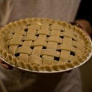 Lattice Pie being held by someone in an apron