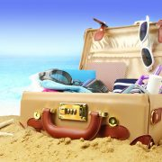 open suitcase on a beach with beach gear inside