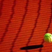 green tennis ball bouncing off of a red clay court with the shadow of the net across the court