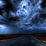 dark storm clouds at night over a paved road without any structures or trees around