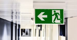 Green emergency exit graphic sign with human figure running through a door and an arrow pointing left