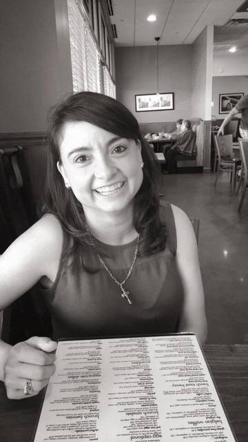 Lisa Lopez smiling, sitting at a table in a restaurant, with a menu in front of her
