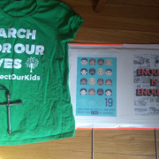 The author's sign and shirt for March for Our Lives. The Cross in both is made from parts of an AK47.