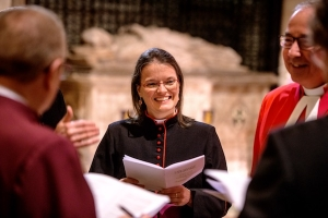 a shorter woman with glasses, smiling, standing in a circle with several male colleagues, all dressed in various church vestments