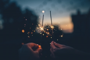 twilight with two hands holding lit sparklers