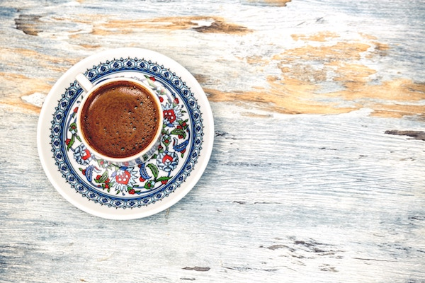 dark coffee in small cup with saucer decorated with flowers on a wooden table top, looking from the top