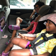two young girls sitting in car seats in the back seat of a car, smiling and watching a program on a screen mounted on the back of the front seats
