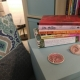 a pile of books about fertility and mothering on a side table in a room with a chair with a pillow