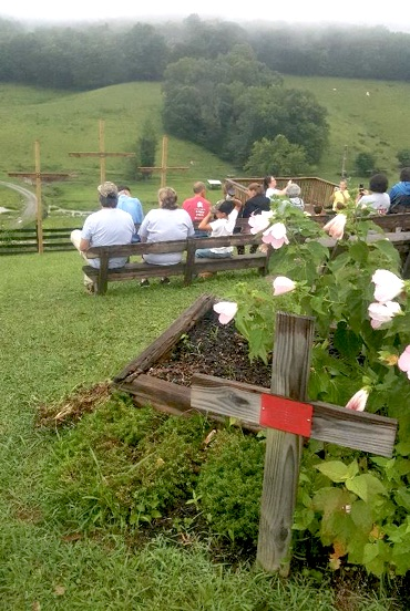 people sitting on benches on a hill facing away from camera and toward three wooden crosses with another wooden cross and flowers in the foreground