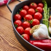 cherry tomatoes, garlic, red peppers and herbs in a cast-iron pan on a wooden table next to a red and white gingham checked cloth
