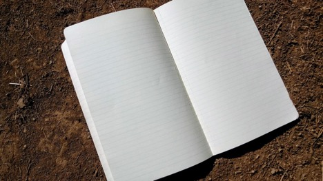 A lined paper notebook sitting open to blank pages on top of some soil.