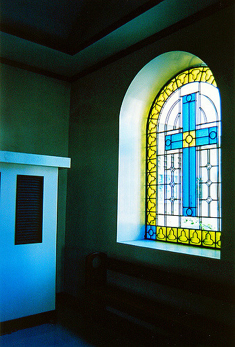 a plain confessional box with a small window next to an arched stained glass window with a cross in the middle and light streaming through