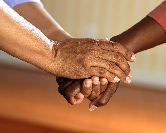 one hand being held between a pair of other hands