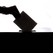 silhouette image of a hand placing a piece of paper into a slot in the top of a box