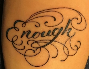 "a black-ink tattoo of the word ""enough"" with curlicue decorations around it"