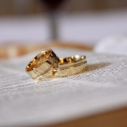 two gold rings on top of a Bible