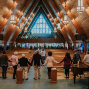 Group of people holding hands around an A-frame wooden church sanctuary