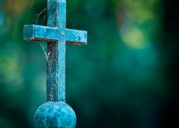 stone cross on ball with spiderwebs